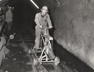 Nous sommes à 400 mètres sous terre. Un ouvrier de l'entretien au fond sur un vélo-mine qui lui permet de rejoindre plus rapidement qu'en marchant l'endroit où il doit se rendre : il peut y avoir plusieurs kilo- mètres entre le puits de descente - Bois 2 ou Bois 3 - et le lieu d'intervention. Les galeries allaient jusqu'à Bourg l'Évêque.